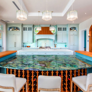 Photo of a mid-sized beach style single-wall open plan kitchen in Tampa with an undermount sink, shaker cabinets, blue cabinets, soapstone benchtops, blue splashback, subway tile splashback, panelled appliances, light hardwood floors, multiple islands, brown floor and grey benchtop.