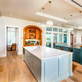 タンパの中くらいのビーチスタイルのおしゃれなキッチン (アンダーカウンターシンク、ソープストーンカウンター、青いキッチンパネル、サブウェイタイルのキッチンパネル、パネルと同色の調理設備、淡色無垢フローリング、茶色い床、グレーのキッチンカウンター、落し込みパネル扉のキャビネット、ターコイズのキャビネット) の写真