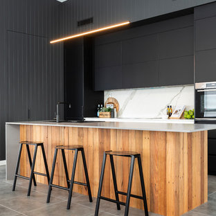 Photo of a large contemporary l-shaped kitchen in Canberra - Queanbeyan with black cabinets, quartz benchtops, white splashback, porcelain splashback, black appliances, porcelain floors, grey floor, a drop-in sink, flat-panel cabinets and with island.