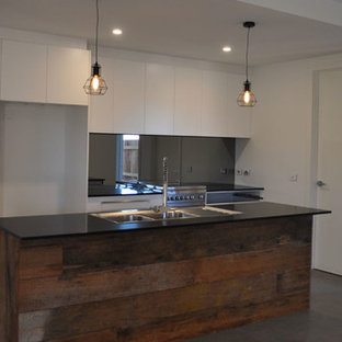 This is an example of a medium sized urban galley kitchen/diner in Canberra - Queanbeyan with a double-bowl sink, flat-panel cabinets, white cabinets, granite worktops, grey splashback, mirror splashback, stainless steel appliances, ceramic flooring and an island.