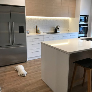 This is an example of a large scandinavian galley separate kitchen in Christchurch with a double-bowl sink, flat-panel cabinets, white cabinets, quartz benchtops, grey splashback, porcelain splashback, stainless steel appliances, with island, brown floor and vinyl floors.