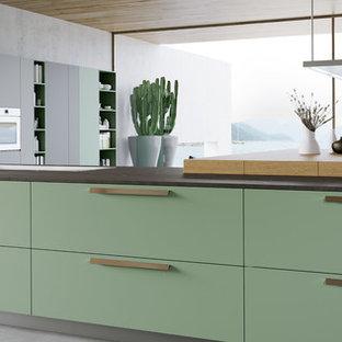 トロントの大きいモダンスタイルのおしゃれなキッチン (ドロップインシンク、フラットパネル扉のキャビネット、緑のキャビネット、木材カウンター、シルバーの調理設備の、コンクリートの床、グレーの床) の写真