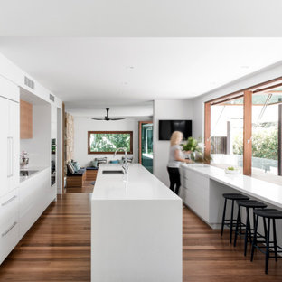 Design ideas for a contemporary galley kitchen in Sunshine Coast with an undermount sink, flat-panel cabinets, white cabinets, panelled appliances, medium hardwood floors, with island, brown floor and white benchtop.
