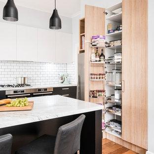 メルボルンの中サイズのインダストリアルスタイルのおしゃれなキッチン (一体型シンク、フラットパネル扉のキャビネット、黒いキャビネット、クオーツストーンカウンター、白いキッチンパネル、サブウェイタイルのキッチンパネル、シルバーの調理設備の、無垢フローリング、ベージュの床、白いキッチンカウンター) の写真