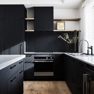 メルボルンの中サイズのインダストリアルスタイルのおしゃれなキッチン (ダブルシンク、フラットパネル扉のキャビネット、黒いキャビネット、コンクリートカウンター、黒いキッチンパネル、モザイクタイルのキッチンパネル、黒い調理設備、無垢フローリング、ベージュの床、グレーのキッチンカウンター) の写真