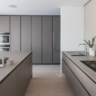 Photo of a large modern grey and white u-shaped kitchen in London with a submerged sink, flat-panel cabinets, grey cabinets, integrated appliances, an island, beige floors and grey worktops.
