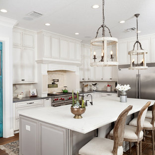 Modelo de cocina rústica, grande, con suelo de madera en tonos medios, puertas de armario turquesas, electrodomésticos de acero inoxidable, una isla y suelo marrón