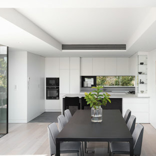 This is an example of a mid-sized modern u-shaped eat-in kitchen in Sydney with flat-panel cabinets, white cabinets, quartz benchtops, grey splashback, engineered quartz splashback, black appliances, ceramic floors, grey floor, grey benchtop, a peninsula and recessed.