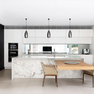 Design ideas for a large contemporary single-wall eat-in kitchen in Sydney with a double-bowl sink, white cabinets, solid surface benchtops, metallic splashback, mirror splashback, stainless steel appliances, cement tiles, multiple islands, grey floor and white benchtop.