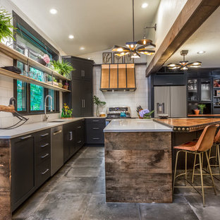 Large industrial eat-in kitchen ideas - Example of a large urban l-shaped gray floor and concrete floor eat-in kitchen design in Manchester with an undermount sink, black cabinets, quartz countertops, white backsplash, porcelain backsplash, stainless steel appliances, an island, white countertops and shaker cabinets