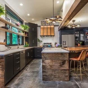 マンチェスターの大きいインダストリアルスタイルのおしゃれなキッチン (アンダーカウンターシンク、黒いキャビネット、クオーツストーンカウンター、白いキッチンパネル、磁器タイルのキッチンパネル、シルバーの調理設備の、グレーの床、白いキッチンカウンター、シェーカースタイル扉のキャビネット、コンクリートの床) の写真