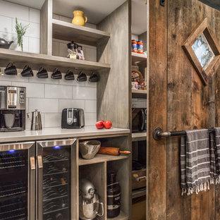 マンチェスターの大きいカントリー風おしゃれなキッチン (アンダーカウンターシンク、フラットパネル扉のキャビネット、黒いキャビネット、クオーツストーンカウンター、白いキッチンパネル、磁器タイルのキッチンパネル、シルバーの調理設備の、セメントタイルの床、グレーの床、白いキッチンカウンター) の写真