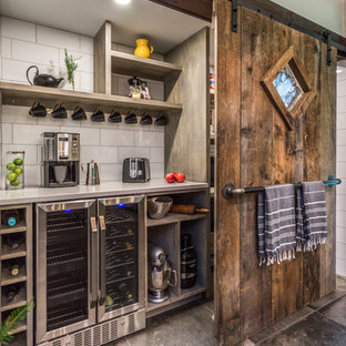 Large eclectic kitchen pantry inspiration - Large eclectic single-wall gray floor and concrete floor kitchen pantry photo in Manchester with quartz countertops, white backsplash, porcelain backsplash, stainless steel appliances, white countertops, open cabinets and gray cabinets
