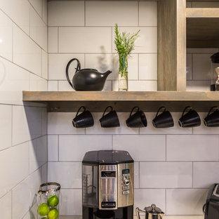Inredning av ett lantligt stort vit vitt kök, med en undermonterad diskho, släta luckor, svarta skåp, bänkskiva i kvarts, vitt stänkskydd, stänkskydd i porslinskakel, rostfria vitvaror, cementgolv, en köksö och grått golv