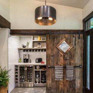Exempel på ett stort lantligt vit vitt kök, med en undermonterad diskho, släta luckor, svarta skåp, bänkskiva i kvarts, vitt stänkskydd, stänkskydd i porslinskakel, rostfria vitvaror, cementgolv, en köksö och grått golv
