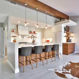 Mid-sized midcentury l-shaped open plan kitchen in Toronto with an undermount sink, flat-panel cabinets, white cabinets, quartz benchtops, white splashback, stone slab splashback, white appliances, vinyl floors, with island and beige floor.