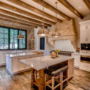 Foto de cocina mediterránea con armarios estilo shaker, puertas de armario blancas, salpicadero blanco, electrodomésticos negros, suelo de madera en tonos medios y dos o más islas