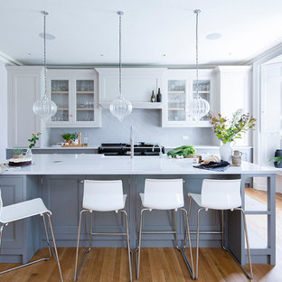 Inspiration for a traditional kitchen in Other with engineered stone countertops, grey cabinets, beige floors, glass-front cabinets, grey splashback, black appliances, light hardwood flooring and an island.