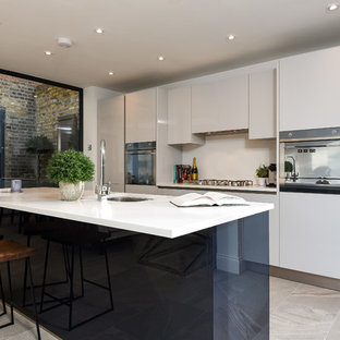 Design ideas for a large contemporary open plan kitchen in London with a double-bowl sink, flat-panel cabinets, laminate countertops, grey splashback, stone slab splashback, stainless steel appliances and an island.