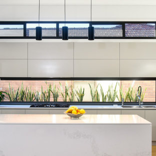 Contemporary galley kitchen in Sydney with a double-bowl sink, flat-panel cabinets, white cabinets, window splashback, medium hardwood floors, with island, brown floor and white benchtop.