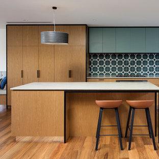 Inspiration pour une cuisine américaine design en L avec un évier 2 bacs, un placard à porte plane, des portes de placard en bois brun, une crédence bleue, un électroménager en acier inoxydable, un sol en bois brun, un îlot central et un sol marron.