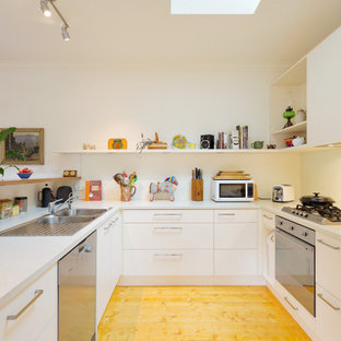 Contemporary u-shaped kitchen in Other with a drop-in sink, flat-panel cabinets, white cabinets, stainless steel appliances, light hardwood floors, a peninsula, beige floor and white benchtop.