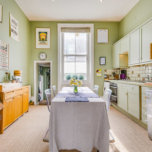 Inspiration for a mid-sized traditional single-wall eat-in kitchen in London with a double-bowl sink, recessed-panel cabinets, green cabinets, wood benchtops, beige splashback, ceramic splashback, stainless steel appliances, carpet, no island, beige floor and green benchtop.