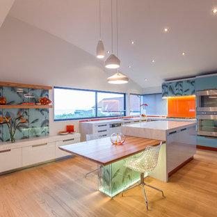Moderne Küche mit flächenbündigen Schrankfronten, blauen Schränken und Küchenrückwand in Orange in Auckland