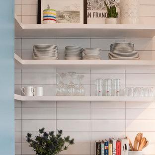 Foto de cocina en L, actual, pequeña, abierta, con fregadero bajoencimera, armarios abiertos, puertas de armario azules, salpicadero blanco, salpicadero de azulejos de cerámica, electrodomésticos de acero inoxidable y una isla