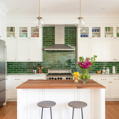Example of a mid-sized transitional u-shaped medium tone wood floor and brown floor kitchen design in San Francisco with an undermount sink, shaker cabinets, white cabinets, green backsplash, subway tile backsplash, stainless steel appliances, an island and marble countertops