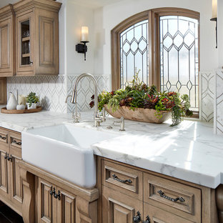 Design ideas for a large beach style u-shaped eat-in kitchen in Orange County with a farmhouse sink, glass-front cabinets, beige cabinets, marble benchtops, white splashback, stone tile splashback, stainless steel appliances, dark hardwood floors, with island and brown floor.