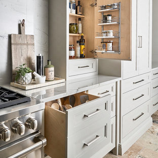 This is an example of a large eclectic l-shaped eat-in kitchen in Other with recessed-panel cabinets, grey cabinets, quartzite benchtops, white splashback, stone slab splashback, panelled appliances, travertine floors, with island, multi-coloured floor, white benchtop and an undermount sink.