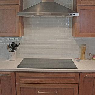 オースティンの大きいトランジショナルスタイルのおしゃれなキッチン (アンダーカウンターシンク、シェーカースタイル扉のキャビネット、中間色木目調キャビネット、クオーツストーンカウンター、黄色いキッチンパネル、ガラスタイルのキッチンパネル、シルバーの調理設備、磁器タイルの床) の写真