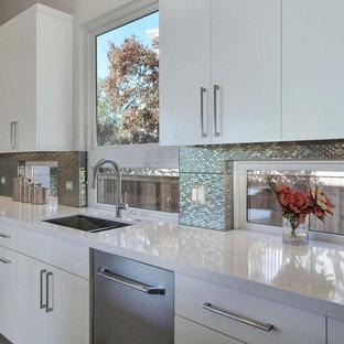 Foto di una grande cucina design con lavello sottopiano, ante lisce, ante bianche, top in quarzo composito, paraspruzzi a effetto metallico, paraspruzzi con piastrelle di metallo, elettrodomestici in acciaio inossidabile, pavimento in gres porcellanato e isola