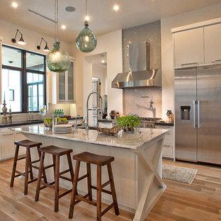 Klassische Küche mit flächenbündigen Schrankfronten, Küchengeräten aus Edelstahl, Marmor-Arbeitsplatte, weißen Schränken, Küchenrückwand in Grau und Rückwand aus Glasfliesen in Austin