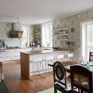 This is an example of a mid-sized eclectic u-shaped eat-in kitchen in Stockholm with wood benchtops, white cabinets, stainless steel appliances, medium hardwood floors, no island and recessed-panel cabinets.
