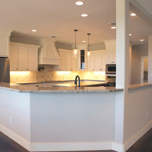 Große Klassische Küche in U-Form mit profilierten Schrankfronten, weißen Schränken, Granit-Arbeitsplatte, Küchenrückwand in Beige, Rückwand aus Travertin, Küchengeräten aus Edelstahl, Betonboden, Kücheninsel und braunem Boden in Houston