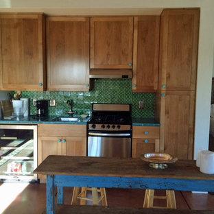 フェニックスの中くらいのサンタフェスタイルのおしゃれなキッチン (シングルシンク、シェーカースタイル扉のキャビネット、中間色木目調キャビネット、タイルカウンター、緑のキッチンパネル、テラコッタタイルのキッチンパネル、コンクリートの床、シルバーの調理設備) の写真