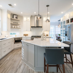 Large transitional eat-in kitchen inspiration - Example of a large transitional l-shaped brown floor and porcelain floor eat-in kitchen design in Atlanta with an undermount sink, shaker cabinets, white cabinets, white backsplash, subway tile backsplash, stainless steel appliances, an island, white countertops and marble countertops