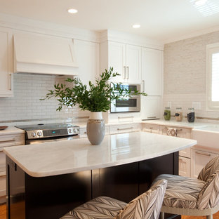 This is an example of a mid-sized transitional l-shaped eat-in kitchen in Baltimore with a farmhouse sink, recessed-panel cabinets, white cabinets, marble benchtops, white splashback, subway tile splashback, stainless steel appliances, medium hardwood floors, with island, brown floor and white benchtop.