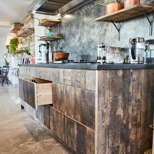 他の地域の広いインダストリアルスタイルのおしゃれなキッチン (アンダーカウンターシンク、フラットパネル扉のキャビネット、中間色木目調キャビネット、亜鉛製カウンター、グレーのキッチンパネル、シルバーの調理設備、コンクリートの床、グレーの床、グレーのキッチンカウンター) の写真