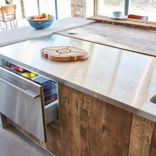 他の地域の大きいインダストリアルスタイルのおしゃれなキッチン (アンダーカウンターシンク、フラットパネル扉のキャビネット、中間色木目調キャビネット、亜鉛製カウンター、グレーのキッチンパネル、シルバーの調理設備の、コンクリートの床、グレーの床、グレーのキッチンカウンター) の写真