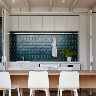 Mid-sized contemporary galley kitchen in Melbourne with a drop-in sink, flat-panel cabinets, grey cabinets, wood benchtops, blue splashback, panelled appliances, medium hardwood floors, with island, beige floor and beige benchtop.