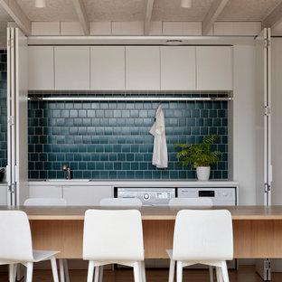 メルボルンの中サイズのコンテンポラリースタイルのおしゃれなキッチン (ドロップインシンク、フラットパネル扉のキャビネット、グレーのキャビネット、木材カウンター、青いキッチンパネル、パネルと同色の調理設備、無垢フローリング、ベージュの床、ベージュのキッチンカウンター) の写真