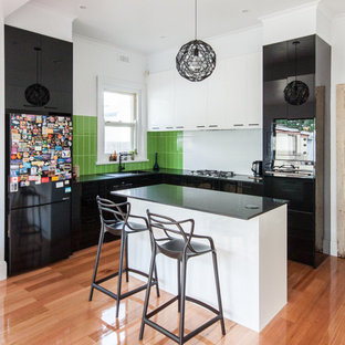 Inspiration for a contemporary l-shaped kitchen in Melbourne with a drop-in sink, flat-panel cabinets, black cabinets, green splashback, medium hardwood floors, with island, brown floor and black benchtop.