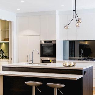 Inspiration för mellanstora klassiska flerfärgat kök, med en undermonterad diskho, släta luckor, vita skåp, bänkskiva i kvarts, grått stänkskydd, spegel som stänkskydd, rostfria vitvaror, mellanmörkt trägolv, en köksö och gult golv