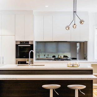 This is an example of a mid-sized contemporary l-shaped open plan kitchen in Melbourne with an undermount sink, flat-panel cabinets, dark wood cabinets, quartz benchtops, metallic splashback, mirror splashback, stainless steel appliances, light hardwood floors, with island, yellow floor and multi-coloured benchtop.