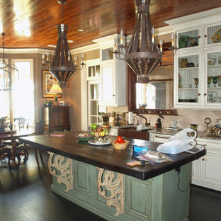 This is an example of a mediterranean eat-in kitchen in Other with a farmhouse sink, raised-panel cabinets, distressed cabinets, wood benchtops, beige splashback, stone tile splashback, panelled appliances, dark hardwood floors, with island, pink floor and grey benchtop.