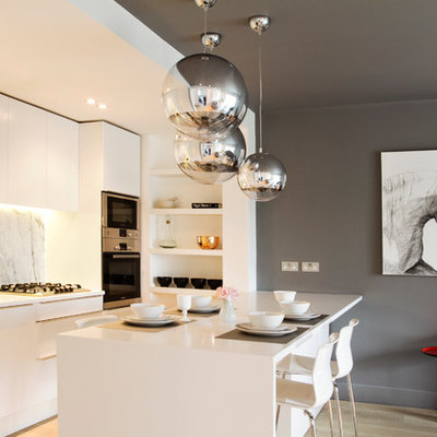 Inspiration for a mid-sized contemporary single-wall light wood floor eat-in kitchen remodel in London with an undermount sink, flat-panel cabinets, white cabinets, solid surface countertops, gray backsplash, marble backsplash, stainless steel appliances and a peninsula