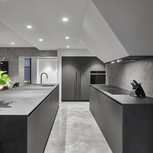 Large modern l-shaped open plan kitchen in Perth with concrete benchtops, grey splashback, stone slab splashback, concrete floors, with island, grey floor, grey benchtop, an undermount sink, flat-panel cabinets, grey cabinets and panelled appliances.